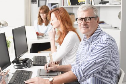 Senior graphic designer sitting at desk and working together with colleagues. Small business.