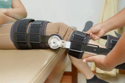 Orthopedist secures leg brace on knee, knee brace support for le